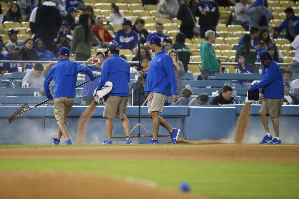 Members of the grounds crew pour dirt near third base after a water pipe broke during the fifth inning of an exhibition baseball game between the Los Angeles Dodgers and the Los Angeles Angels, Tuesday, March 27, 2018, in Los Angeles. (AP Photo/Jae C. Hong)