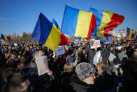Anti-vaccination protesters waving national flags during a rally outside the parliament building in Bucharest, Romania, Sunday, March 7, 2021. Some thousands of anti-vaccination protestors from across Romania converged outside the parliament building protesting against government pandemic control measures as authorities announced new restrictions amid a rise of COVID-19 infections. (AP Photo/Vadim Ghirda)