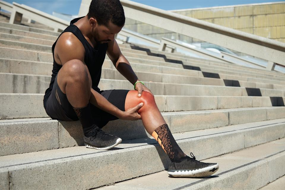 runner with athletic body wearing black running shoes, sitting on steps on concrete stair, clutching injured knee in excruciating pain