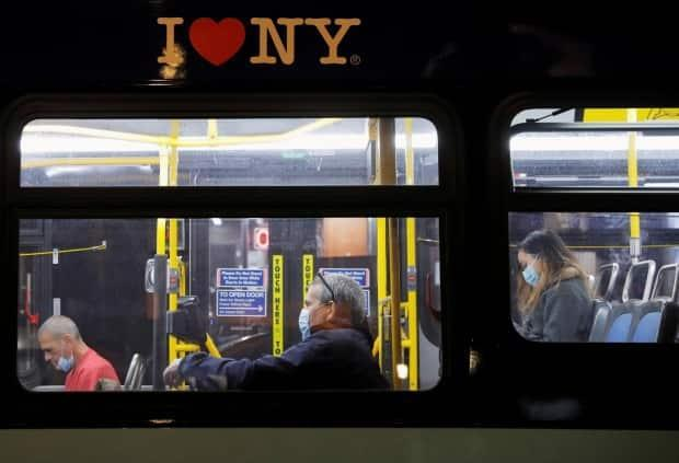 Passengers wear face masks on a bus in Manhattan, New York City, on Nov. 13, 2020. (Andrew Kelly/Reuters - image credit)