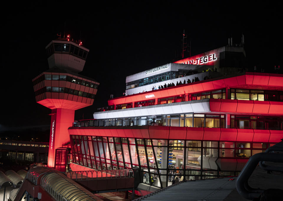 The Tegel Airport is illuminated in red Saturday, Nov. 7, 2020, in Berlin, Germany. The ceremonial last flight is scheduled for Sunday. (Fabian Sommer/dpa via AP)