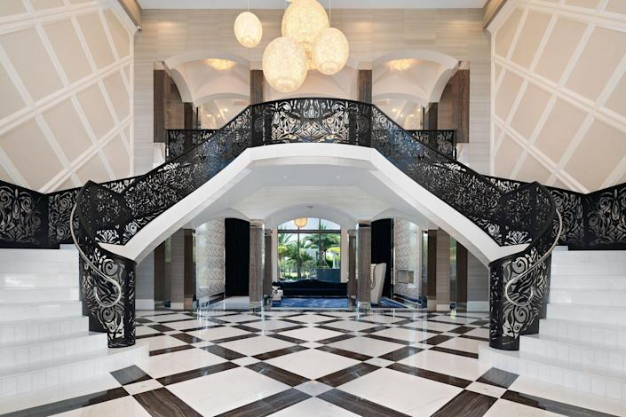 The foyer's custom-designed, open-arms staircase is inspired by old Hollywood.