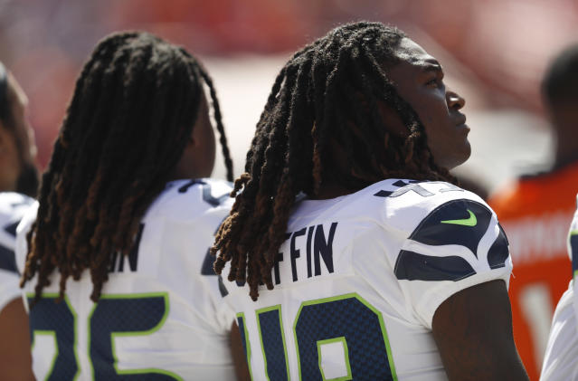 Seattle Seahawks linebacker Shaquem Griffin, right, lines up alongside his brother, left, cornerback Shaquill Griffin, during the playing of the national anthem before an NFL football game against the Denver Broncos, Sunday, Sept. 9, 2018, in Denver. (AP Photo/David Zalubowski)