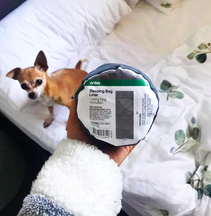 White sheets and dog in background sleeping bag in foreground sleeping bag liner used for fake tan sleeping
