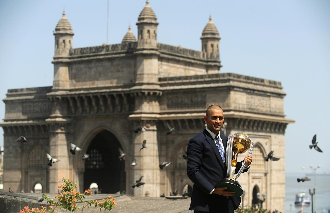 India's cricket team captain Mahendra Singh Dhoni poses with the ICC Cricket World Cup trophy near the Gateway of India during a photo call at the Taj Mahal hotel in Mumbai on April 3, 2011. India won the Cricket World Cup for the first time since 1983 with a six-wicket victory over Sri Lanka on April 2. AFP PHOTO/ Punit PARANJPE (Photo credit should read PUNIT PARANJPE/AFP/Getty Images)