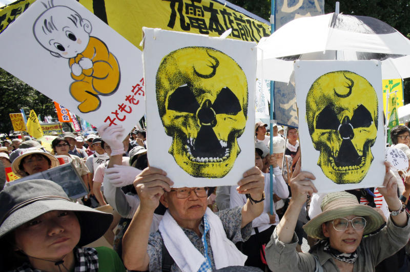 "Protesters carry anti-nuclear placards during a march in Tokyo, Monday, July 16, 2012. Tens of thousands of people gathered at a Tokyo park, demanding ""Sayonara,"" or goodbye, to nuclear power as Japan prepares to restart yet another reactor, and expressed outrage over a report that blamed culture on the Fukushima disaster. The placard at left reads: ""Protect children."" (AP Photo/Koji Sasahara)"