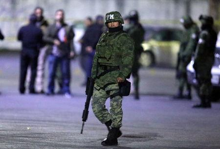 A soldier stands guard next to a crime scene, where men were killed inside a home by unknown assailants, in the municipality of San Nicolas de los Garza, Mexico, January 27, 2018. Picture taken January 27, 2018. REUTERS/Jorge Lopez