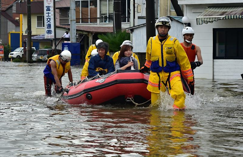 Rescue workers transport evacuees in a rubber boat through floodwaters at Oyama in Tochigi prefecture, north of Tokyo on September 10, 2015 (AFP Photo/Yoshikazu Tsuno)