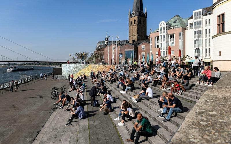 People enjoy the afternoon sun at the river Rhine in the old town of Duesseldorf, Germany, despite the social distancing order to fight the coronavirus pandemic on Friday, April 24, 2020. (AP Photo/Martin Meissner) -  Martin Meissner/ AP