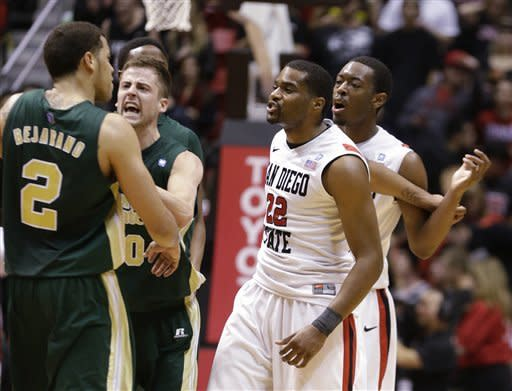Colorado State 's Daniel Bejarano is restrained by teammate Wes Eikmeier during a confrontation with San Diego State's Chase Tapley and Xavier Thames, right rear, late in the overtime period of San Diego State's 79-72 victory in an NCAA college basketball game Saturday Jan. 12, 2013, in San Diego. (AP Photo/Lenny Ignelzi)