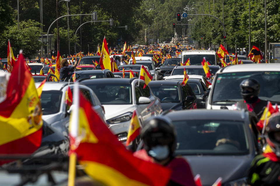 People wave Spanish flags during a drive-in protest organised by Spain's far-right Vox party against the Spanish government's handling of the nation's coronavirus outbreak in Madrid, Spain Saturday, May 23, 2020. (AP Photo/Manu Fernandez)
