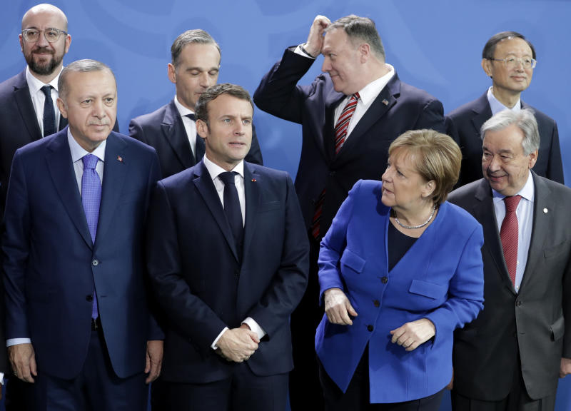 German Chancellor Angela Merkel, front second left, waits for the arrival of leaders prior to a group photo at a conference on Libya at the chancellery in Berlin, Germany, Sunday, Jan. 19, 2020. Front row left to right, Turkish President Recep Tayyip Erdogan, French President Emmanuel Macron, and United Nations Secretary General Antonio Guterres. Back row left to right, European Council President Charles Michel, German Foreign Minister Heiko Maas, U.S. Secretary of State Mike Pompeo and Chinese State Councilor Yang Jiechi. (AP Photo/Michael Sohn)