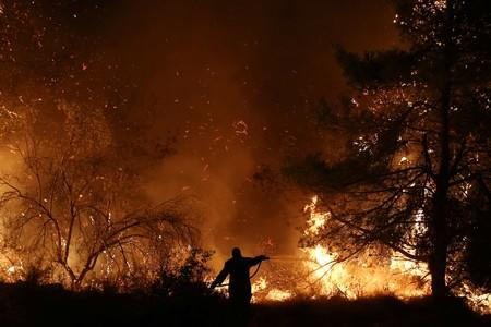 A firefighter tries to extinguish a wildfire burning near the village of Makrimalli on the island of Evia