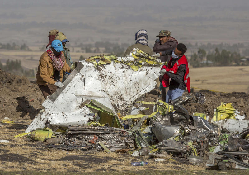 FILE - In this file photo dated Monday, March 11, 2019, rescuers work at the scene of an Ethiopian Airlines plane crash south of Addis Ababa, Ethiopia.  The number of deaths in major air crashes around the globe fell by more than half in 2019 according to a report released Wednesday Jan. 1, 2020, by the aviation consultancy To70, revealing the worst crash for the year was an Ethiopian Airlines Boeing 737 MAX on March 10 that lost 157 lives. (AP Photo/Mulugeta Ayene, FILE)