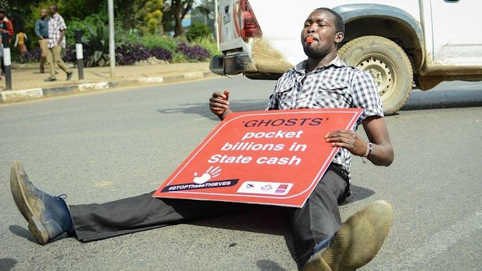 A man sitting on the floor with a placard (2018 archive shot)