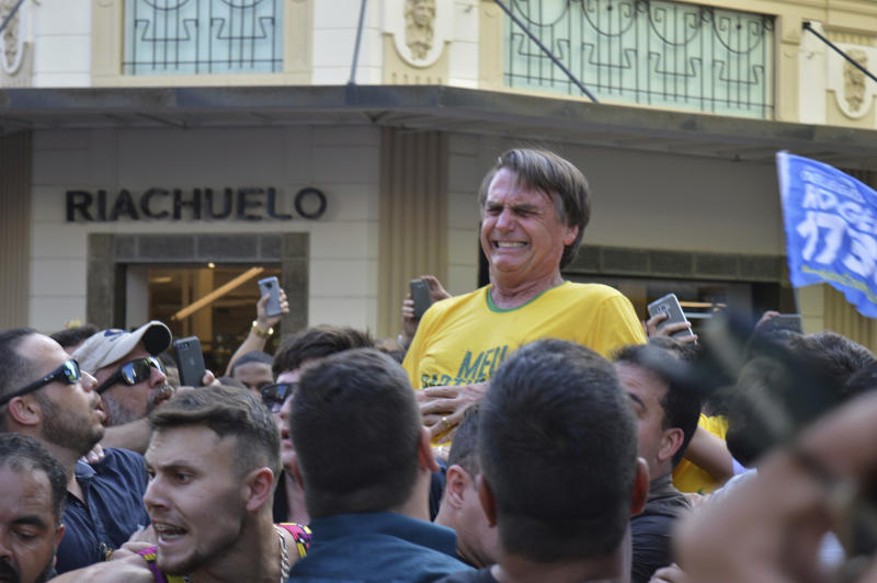 FILE - In this Sept. 6, 2018 file photo, presidential candidate Jair Bolsonaro grimaces right after being stabbed in the stomach during a campaign rally in Juiz de Fora, Brazil. A Brazilian judge has ruled on Monday, May 27, 2019, that the man charged with nearly killing Bolsonaro last year should not be punished because he is mentally ill. (AP Photo/Raysa Leite, File)