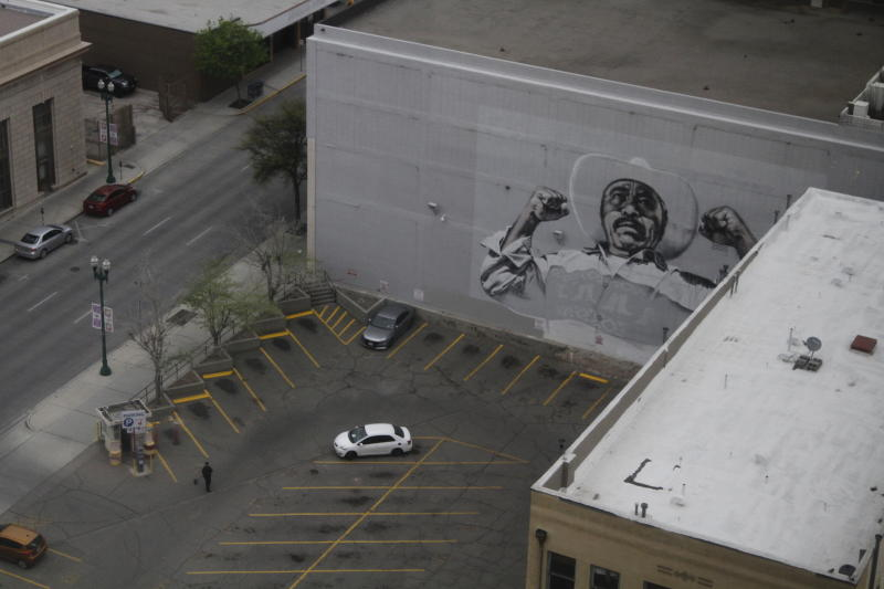 In this Wednesday, March 18, 2020 photo, a woman sweeps a nearly empty parking lot in downtown El Paso, Texas, as seen from the office building of Congresswoman Veronica Escobar, D-Texas. Traffic slowed in the city after sweeping measures to reduce the spread of COVID-19. After closing her office to in-person visits, Escobar held a virtual town hall for constituents to ask questions about government's response to the coronavirus. (AP Photo/Cedar Attanasio)