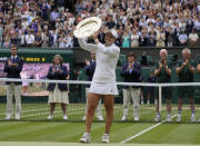 Australia's Ashleigh Barty poses with the trophy for the media after winning the women's singles final, defeating the Czech Republic's Karolina Pliskova on day twelve of the Wimbledon Tennis Championships in London, Saturday, July 10, 2021. (AP Photo/Kirsty Wigglesworth)