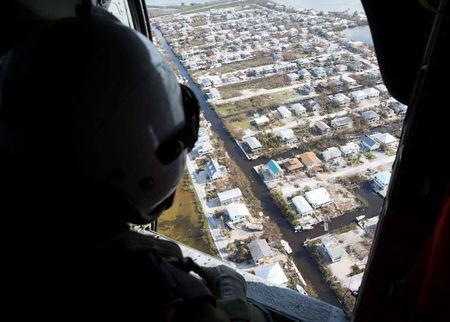 Naval Air Crewman (Helicopter) 3rd Class Austin Rivera, from Fayetteville, N.C., assigned to the Dragon Whales of Helicopter Sea Combat Squadron (HSC) 28, surveys damage caused by Hurricane Irma in the Florida Keys, Florida, U.S. in this handout photo obtained by Reuters September 15, 2017. Mass Communication Specialist 2nd Class Kristopher Ruiz/U.S. Navy/Handout via REUTERS