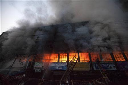 Locals and fire-fighters try to control a fire at a garment factory in Dhaka