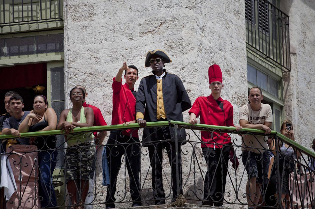 Workers at the La Moneda Cubana restaurant stand on a balcony to watch the arrival of U.S. singer Beyonce and her husband, rapper Jay-Z, in Old Havana, Cuba, Thursday, April 4, 2013. R&B's power couple is in Havana on their fifth wedding anniversary. (AP Photo/Ramon Espinosa)