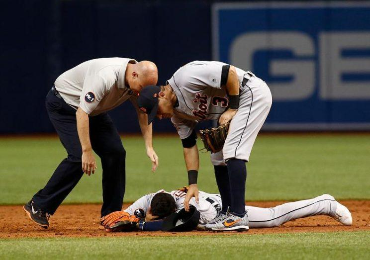 Tigers shortstop Jose Iglesias is tended to after an awkward collision and game-ending throwing error. (Getty Images)