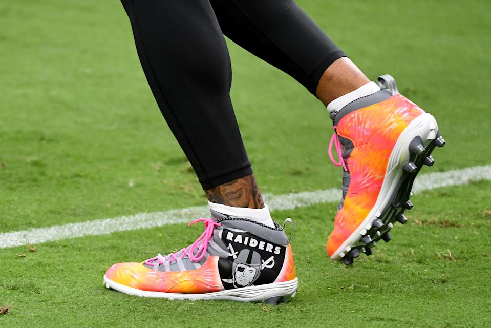 Darren Waller's pink and orange cleats with the Raiders logo on them.