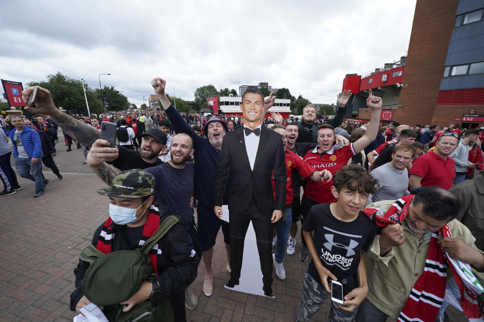 Fans poses for selfies with a cutout of Manchester United's Cristiano Ronaldo before the English Premier League soccer match between Manchester United and Newcastle United at Old Trafford stadium in Manchester, England, Saturday, Sept. 11, 2021. (AP Photo/Jon Super)