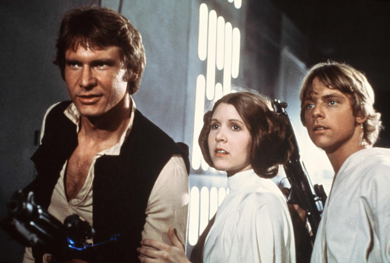 "FILE - This file publicity image provided by 20th Century-Fox Film Corporation shows Harrison Ford, as Han Solo, Carrie Fisher, as Princess Leia Organa, and Mark Hamill, as Luke Skywalker. in a scene from the 1977 ""Star Wars"" movie released by 20th Century-Fox.  (AP Photo/20th Century-Fox Film Corporation, File)"