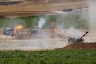 An Israeli military artillery unit fires a shell, as seen from the Israeli side of the border with the Gaza Strip