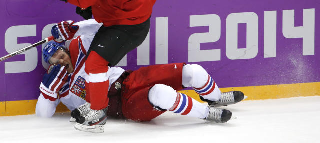 Czech Republic defenseman Zbynek Michalek slides into the boards against Switzerland in the second period of a men's ice hockey game at the 2014 Winter Olympics, Saturday, Feb. 15, 2014, in Sochi, Russia. (AP Photo/Petr David Josek)