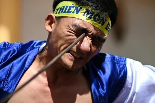 Le Van Thang, 28, student of the centuries-old martial art of Thien Mon Dao, bends a construction rebar against his eye socket inside the Bach Linh temple compound at Du Xa Thuong village in Hanoi