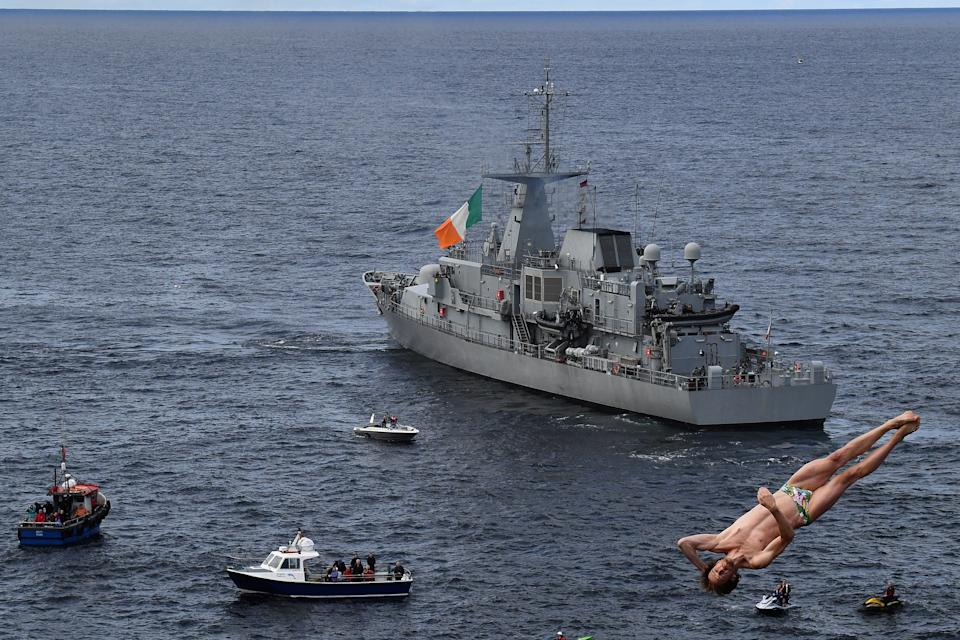Gary Hunt of France dives past an Irish Naval vessel called the LE Niamh during the 2021 Cliff Diving World Series in Downpatrick Head, Ireland, September 12, 2021. REUTERS/Clodagh Kilcoyne