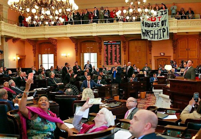"""Some members of the Ohio House applaud following their vote while others photograph protestors who unfurled banners reading """"This is not a House of Worship"""" and """"This is not a Doctor's office"""" following a vote on the Heartbeat Bill at the Ohio Statehouse in Columbus, Ohio on Wednesday, April 10, 2019. The House members voted in the controversial """"Heartbeat Bill"""" that bans abortion at the first sounds of a fetal heartbeat, which is around 6 weeks after conception. Many protestors shouted in the hallway outside of the meeting where House members decided to pass the bill. (Brooke LaValley/The Columbus Dispatch via AP)"""