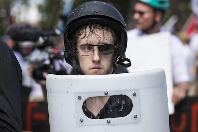 <p>A White Supremacists with one lens knocked out of his sunglasses holds up a shield during clashes with counter protestors at Emancipation Park where the White Nationalists are protesting the removal of the Robert E. Lee monument in Charlottesville, Va., on Aug. 12, 2017. (Photo: Samuel Corum/Anadolu Agency/Getty Images) </p>
