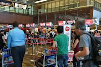 Passengers queue at the AirAsia check-in counter before their departure at Singapore Changi airport terminal on December 28, 2014