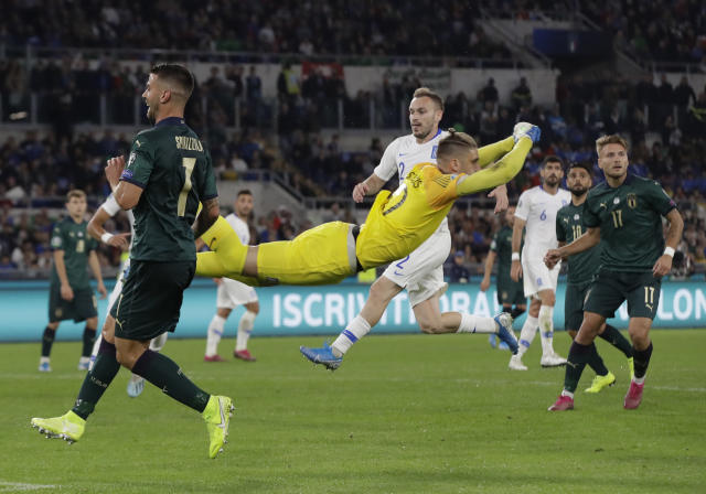 Greece's goalkeeper Alexandros Paschalakis flies through the air after he punches the ball clear as Italy's Lorenzo Pellegrini looks on during the Euro 2020 group J qualifying soccer match between Italy and Greece in Rome, Italy, Saturday, Oct. 12, 2019. (AP Photo/Alessandra Tarantino)