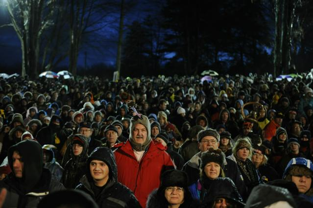 PUNXSUTAWNEY, PA - FEBRUARY 2: A crowd gathers to watch Punxsutawney Phil come out of his burrow during the 125th annual Groundhog Day festivities on February 2, 2011 in Punxsutawney, Pennsylvania. Phil came out and did not see his shadow predicting an early spring. Groundhog Day is a popular tradition in the United States and Canada. A smaller than usual crowd this year of less than 15,000 people spent a night of revelry awaiting the sunrise and the groundhog's exit from his winter den. If Punxsutawney Phil sees his shadow he regards it as an omen of six more weeks of bad weather and returns to his den. Early spring arrives if he does not see his shadow causing Phil to remain above ground. (Photo by Jeff Swensen/Getty Images)