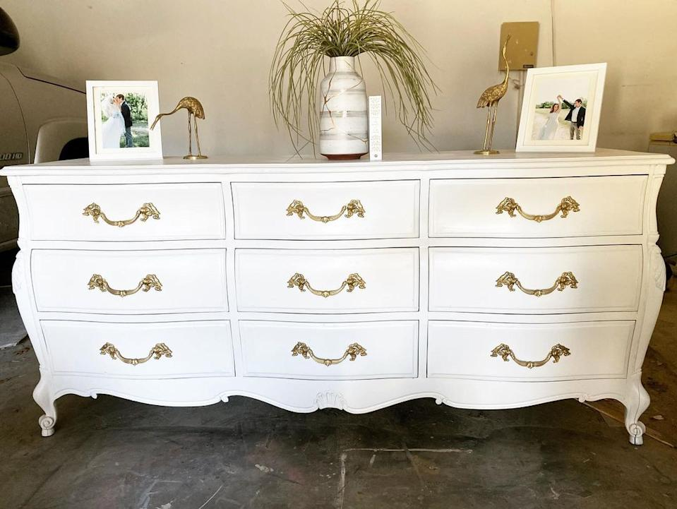 A large vintage white nine-drawer buffet with gold handles