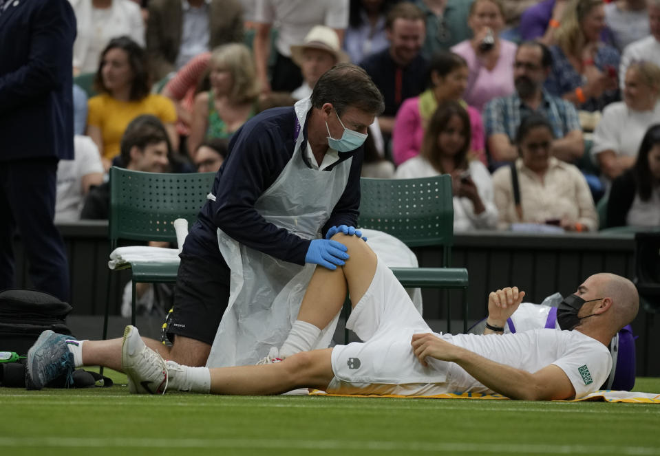 Adrian Mannarino of France receives medical care during the men's singles first round match against Switzerland's Roger Federer on day two of the Wimbledon Tennis Championships in London, Tuesday June 29, 2021. (AP Photo/Kirsty Wigglesworth)