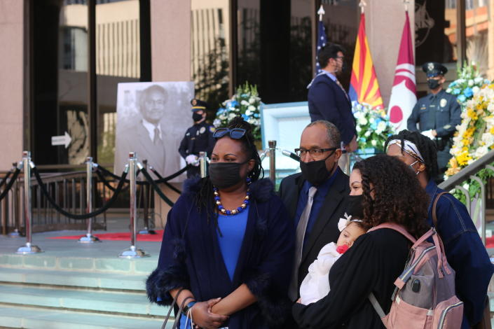 """One of Calvin C. Goode's sons, Vernon """"Zina"""" Goode, poses with members of his family at the open casket viewing of former Phoenix Vice Mayor and city councilman Calvin C. Goode on Saturday, Jan. 9, 2021, in Phoenix, Ariz. Goode died on Wednesday, Dec. 23, 2020. He was 93. (AP Photo/Cheyanne Mumphrey)"""
