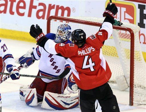 Ottawa Senators' Chris Phillips (4) celebrates a goal by Andre Benoit, not shown, as New York Rangers goalie Henrik Lundvist crouches near during the second period of their NHL hockey game, Thursday, March 28, 2013, in Ottawa, Ontario. (AP Photo/The Canadian Press, Fred Chartrand)