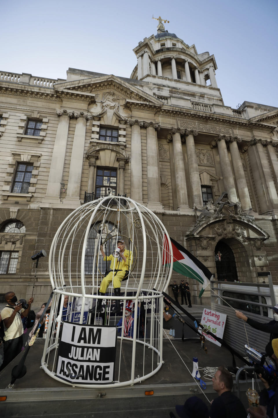 Fashion designer Vivienne Westwood sits suspended in a giant bird cage in protest against the extradition of WikiLeaks founder Julian Assange to the U.S., outside the Old Bailey court, in London, Tuesday, July 21, 2020. Assange is in London's Belmarsh Prison awaiting a full extradition hearing, which has been postponed because of the coronavirus pandemic. Originally due to begin in May, it is now scheduled to start on Sept. 7 at the Old Bailey. (AP Photo/Matt Dunham)