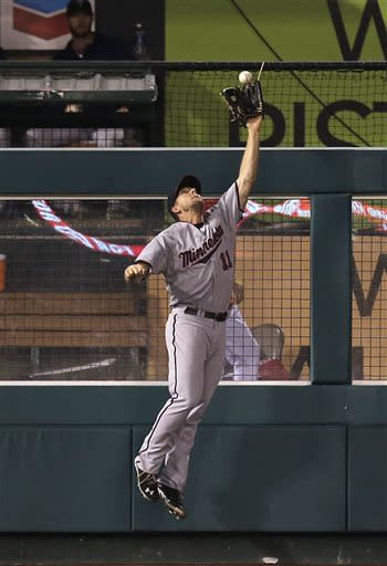 Minnesota Twins left fielder Clete Thomas jumps over the fence to catch a ball hit by Los Angeles Angels' Chris Iannetta during the eighth inning of a baseball game on Monday, July 22, 2013, in Anaheim, Calif. (AP Photo/Jae C. Hong)