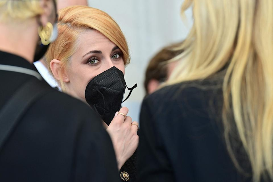 """Kristen Stewart holds her face mask as she attends a photocall for the film """"Spencer"""" at Venice Film Festival."""