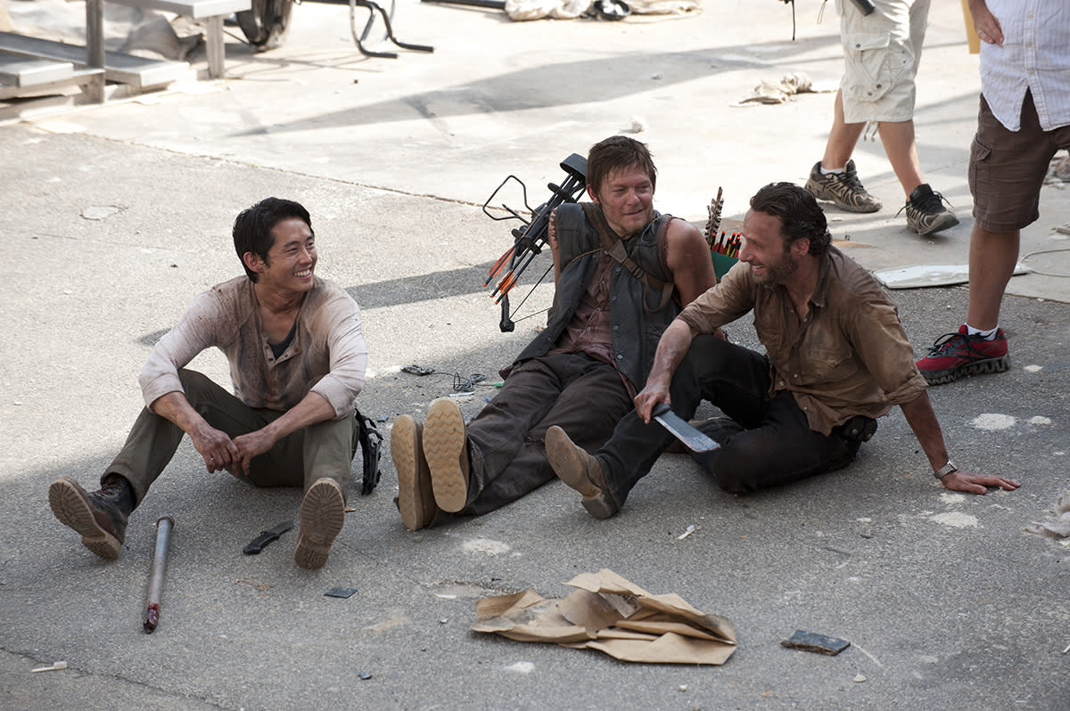 <p>Knives and crossbows and machetes, oh my! Steven Yeun, Norman Reedus, and Andy Lincoln take a break and share a laugh at the prison set.<br /><br />(Photo: AMC) </p>