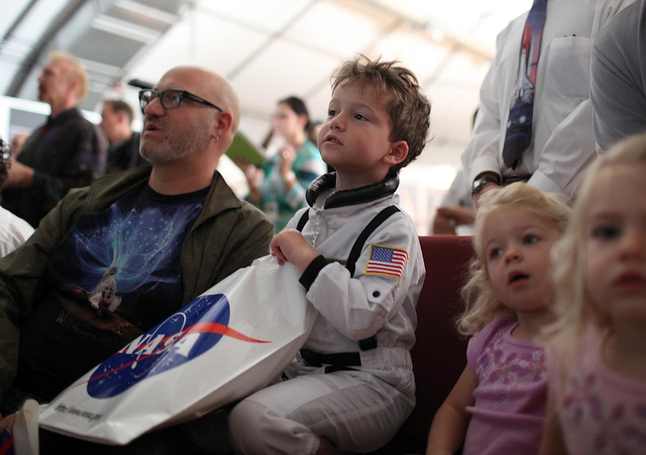 MOFFETT FIELD, CA - JULY 08:  Five year-old Lux Sparks-Pescovitz (R) and his father David Pescovitz (L) watch a live video feed of the launch of space shuttle Atlantis at the NASA reseach center on July 8, 2011 in Moffett Field, California. Space shuttle Atlantis is the final lift off in the 30-year-old shuttle program.  (Photo by Justin Sullivan/Getty Images)