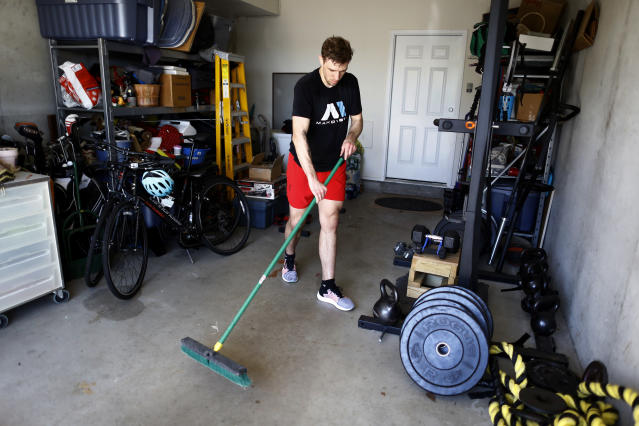 Fighter Kyle Daukaus sweeps out his garage after a training session, Saturday, May 2, 2020, in Philadelphia. Daukaus, a rising star in the regional MMA promotion Cage Fury Fighting Championships, is still chasing his dream of getting the call to fight for UFC despite the coronavirus pandemic. (AP Photo/Matt Slocum)