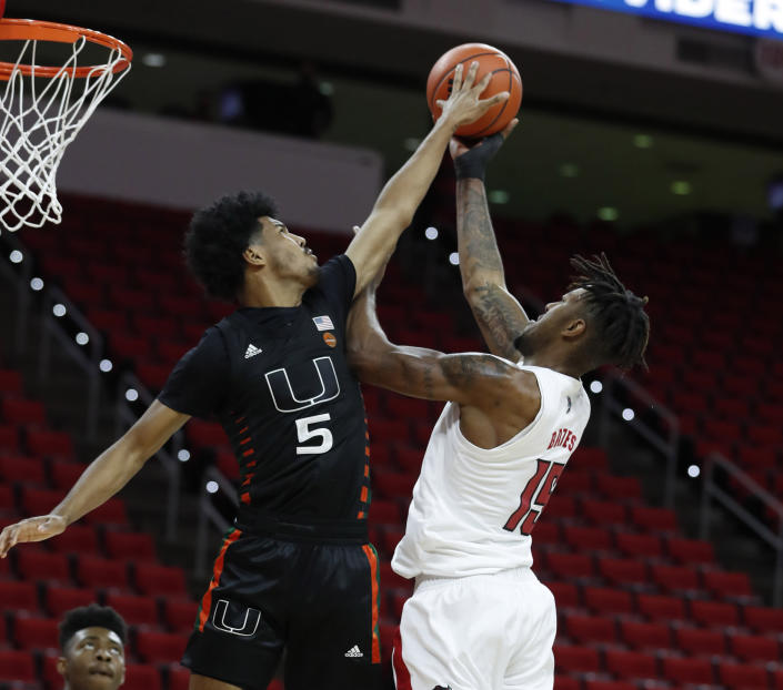 Miami's Harlond Beverly (5) blocks a shot by North Carolina State's Manny Bates (15) during the first half of an NCAA college basketball game at PNC Arena in Raleigh, N.C., Saturday, Jan. 9, 2021. (Ethan Hyman/The News & Observer via AP)