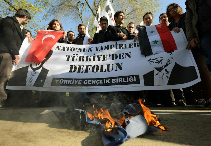 """Turks protest against U.S. Secretary of State John Kerry and the """"Friends of Syria"""" group as it met in Istanbul, Turkey, Saturday, April 20, 2013. Kerry is expected to announce a significant expansion of non-lethal aid to the Syrian opposition. The banner with posters of Kerry and his Turkish counterpart Ahmet Davutoglu read: """" NATO''s vampires get out of Turkey."""" A NATO flag is burning in front.(AP Photo)"""